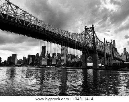 Queensboro bridge over the river, and buildings of the city in black and white style, Manhattan, New York