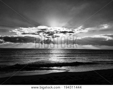 Sunrise behind the cloud on the beach in black and white style, Florida