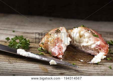 Goat cheese wrapped in smoked fried bacon on wood with knife and parsley