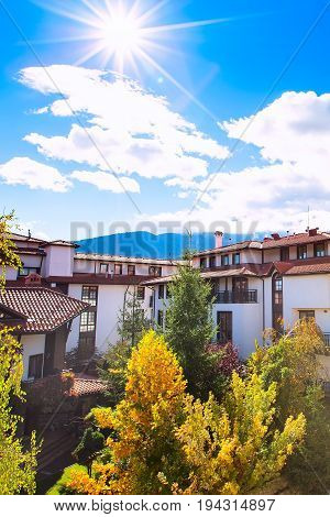 Autumn panorama with nice houses, colorful fall trees and sun on blue sky