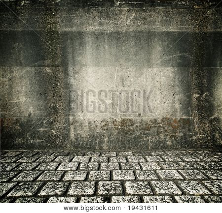 Grungy concrete wall and cobblestone