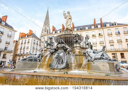 View on the Royal square with fountain and church tower in Nantes city in France