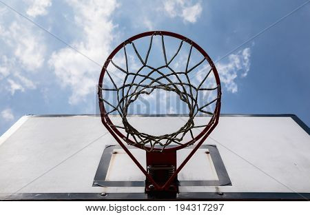 basketball backboard on blue cloudy sky background Outdoor basketball hoop on a cloudy day