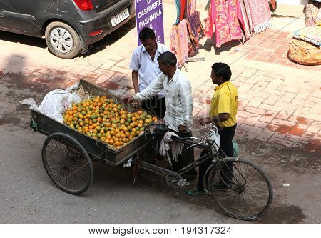 Delhi, India - March 17, 2013: Men of Indians with a bicycle loaded with mandarins. Loy Bazar, Delhi, India.