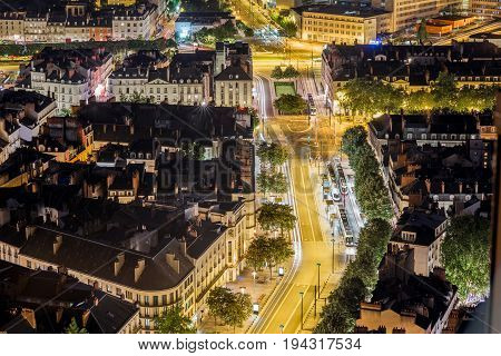 Aerial cityscape view with illuminated buildings and streets in Nantes city during the night in France