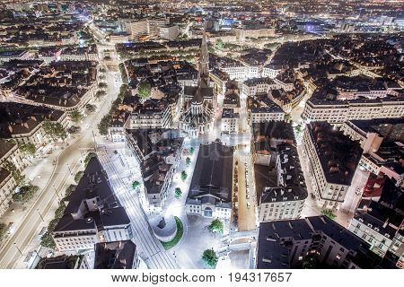 Aerial cityscape view with illuminated streets and buildings in Nantes city during the night in France