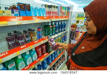 Kota Kinabalu,Sabah,Malaysia-June 17,2017:Muslim woman looking the Listerine Antiseptic Mouthwash bottle in pharmacy of Kota Kinabalu,Sabah,Malaysia.It is a brand of antiseptic mouthwash product.