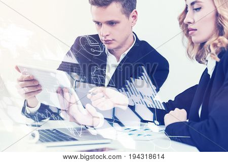 Young man and his gorgeous red haired colleague are discussing their agenda in a white office. The man is holding a tablet. Toned image double exposure.