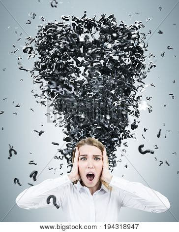 Terrified blonde businesswoman wearing a white blouse standing against a gray wall with a question mark tornado emerging from her head. 3d rendering