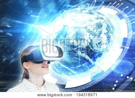 Blond girl in a white dotted blouse wearing VR glasses and standing against a large Earth hologram and an HUD. Toned image double exposure.