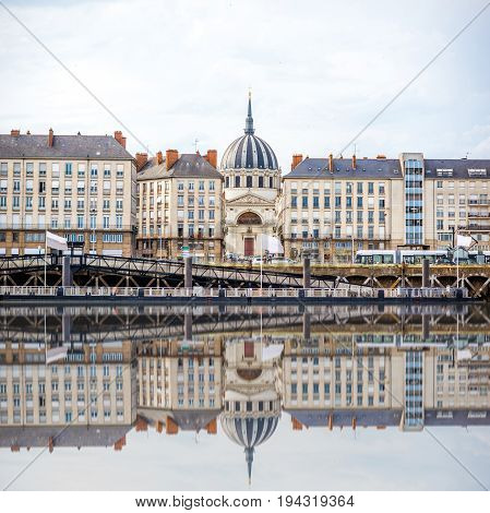 Beautiful riverside view with old buildings and Notre Dame cathedral in Nantes city in France