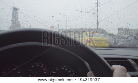 Driver point of view in car's windshield on the city street. Rain in Moscow, may, POV
