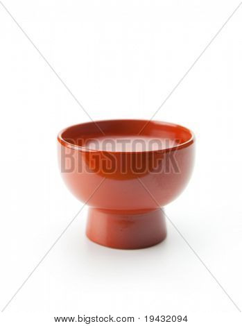 Sake served in a traditional enameled ochoko cup, isolated on white. poster