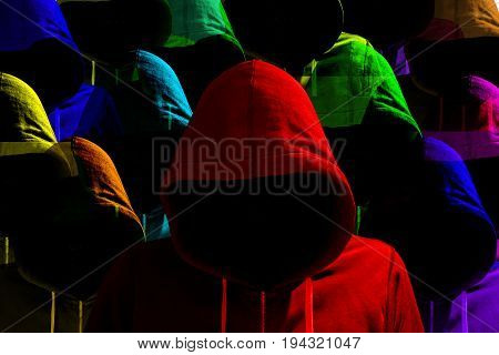 Group of differently colored hooded hackers with side light diversity cybersecurity concept