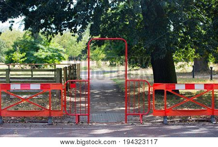 Red barrier and gate blocking the restricted aria in park, London