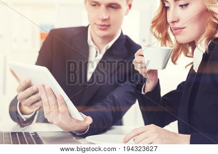 Blond businessman is sitting at a table in a white office and holding a tablet computer. His red haired gorgeous colleague is pointing at a screen. Toned image close up