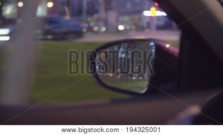 Point of View of the city traffic in car's rearview mirror and side window. Defocused city lights. Moscow, june, POV