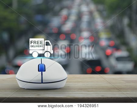 Free delivery truck icon with wireless computer mouse on wooden table over blur of rush hour with cars and road Business transportation concept