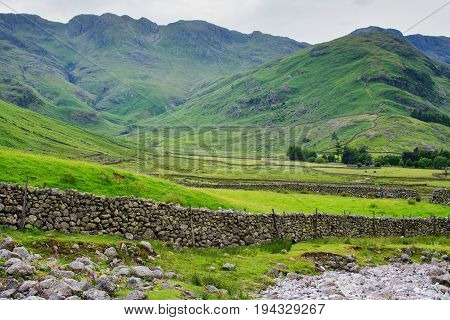 Beautiful landscapes in Lake District National Park, England, stone wall, mountains on the background, selective focus