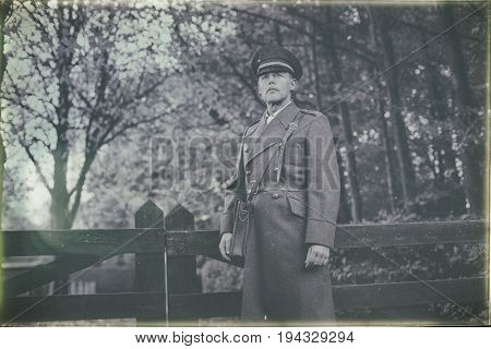 Antique Black And White Photo Look Of 1940S Military Officer Standing At Wooden Fence In Autumn Fore