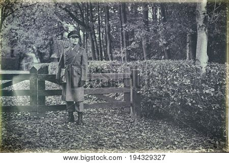 Antique Black And White Photo Of 1940S Military Officer Standing At Wooden Fence In Autumn Forest.
