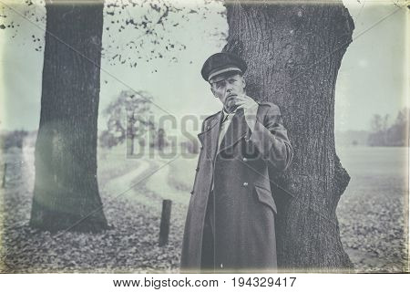 Antique Black And White Photo Of Resting 1940S Military Officer Smoking Cigarette Under Tree.
