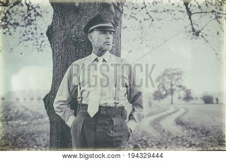 Antique Black And White Photo Of 1940S Military Officer Smoking Cigarette Under Tree.