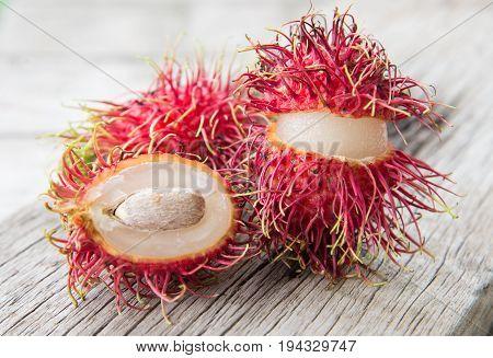 Fresh rambutan thai fruit on wood texture background.