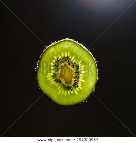 Green slice of kiwi in backlight with dark background
