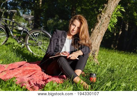 People lifestyle transport and ecology. Portrait of serious young sucessful beautiful Caucasian woman in formal suit having coffee break at park posing at red blanket and making notes in her dairy.