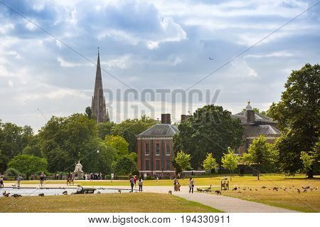 London, UK - September 8, 2016:  Kensington palace, queen Victoria monument in Hyde park view at sunny day with lots of people walking and resting in the park