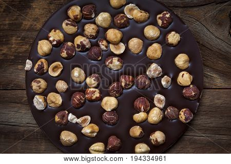 Round artisanal dark chocolate bar with whole hazelnuts on rustic wood background, overhead view