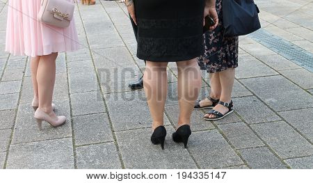 Feet of women and men Everyone has different shoes They stand side by side Background of gray tiles
