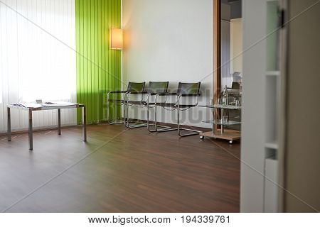 Doctors or dentists empty waiting room with a row of seats against a wall in front of a curtained window and copy space