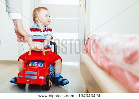 A little child driving around the house