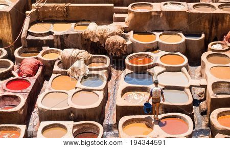 Fez Morocco - May 07 2017: Young unidentifiable man with a bucket standing on the vats of a leather tannery looking at the hides laying in the dye.