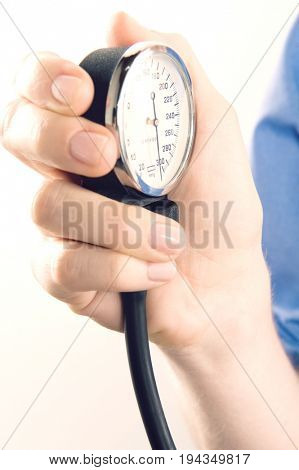 Close up of a female surgeon's hand holding meter of blood pressure equipment