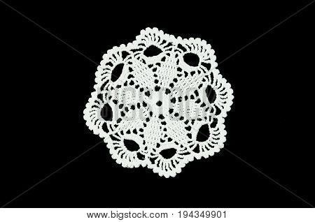 White crocheted coasters on black background. Not isolated. Crochet background. Lace doily.