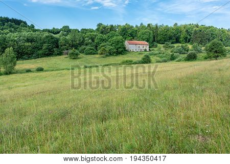 French countryside - Lorraine. Typical landscape with hills, pasture and an old house.