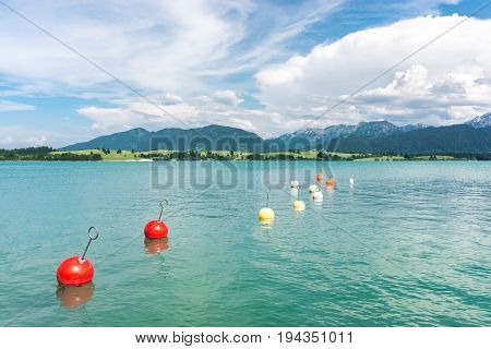 Marker buoys on surface of water. Mountains and thundery clouds. Bavaria, Germany.