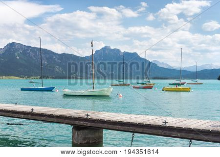 Small sailboats anchoring in alpine lake. Landing stage and mountains framing the boats. Bavaria, Germany, Allgau, Forggensee.