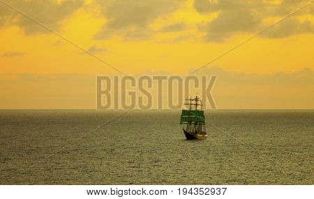 low aerial view of tall sailing ship at sea at sunset with room for text