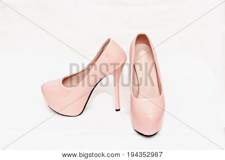 Female pink shoes with high heels isolated against white background.