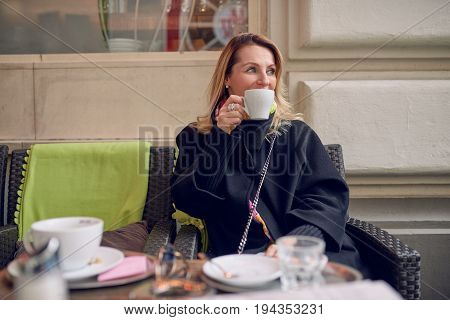 Woman sitting in a restaurant drinking coffee and looking away to her left with a smile as she watches something with the cup obscuring her lower face