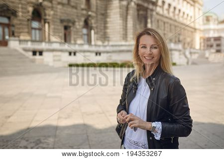 Attractive woman standing in an urban square in front of a large historic building looking at the camera with a warm friendly smile with copy space