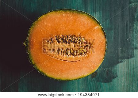 Melon texture and background. Healthy food. Close up view of melon on wooden background. Fresh fruit. Macro view of cut melon surface.