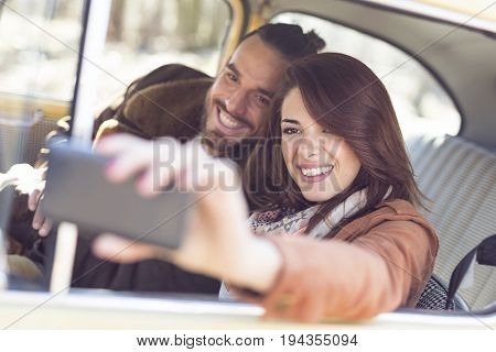 Young couple on a road trip enjoying the sunny day and having fun taking selfie.