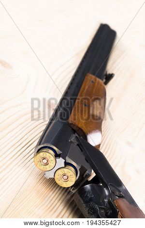 The hunter's gun rests on a table of light wood