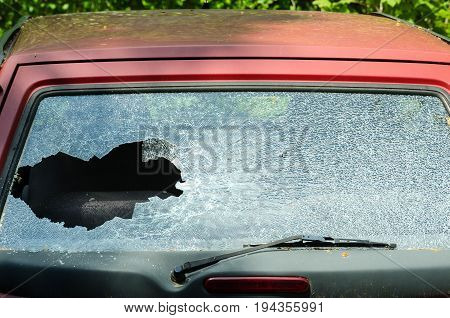 Smashed rear window of the car. Car accident. Damaged car. Windshield glass crack.