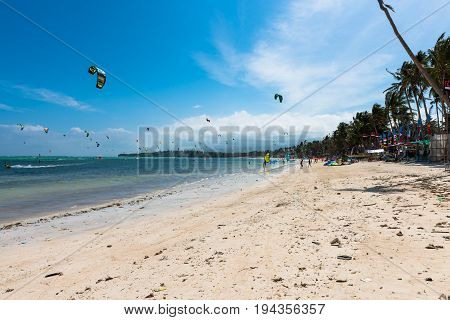 BORACAY, WESTERN VISAYAS, PHILIPPINES - JANUARY 11, 2015: Many people practicing windsurfing and kiteboarding at Bulabog Beach in Boracay.